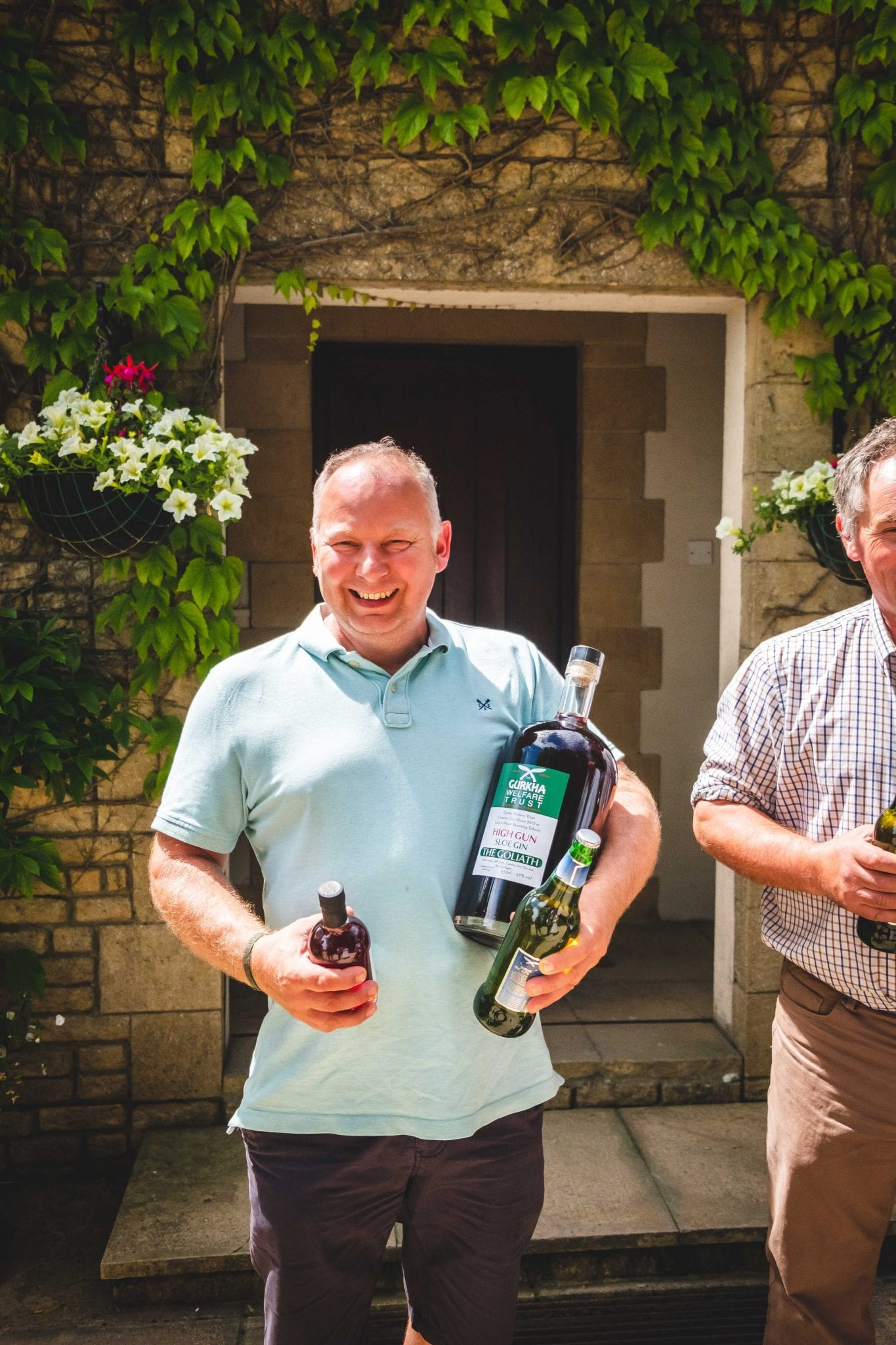 The individual winner from the Gurkha Welfare Trust Charity Shoot at Lady's Wood Shooting School holds his prize of a giant bottle of sloe gin