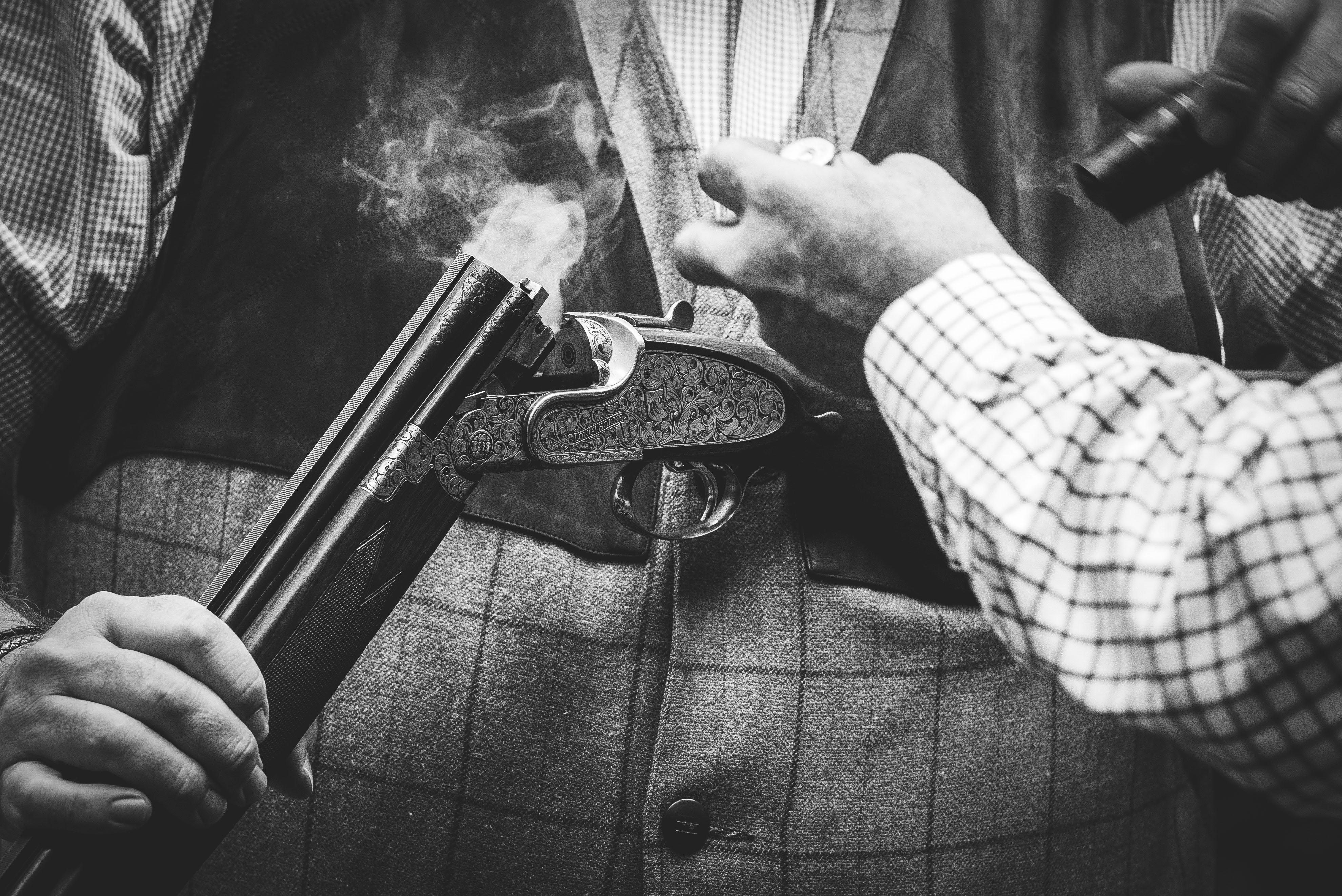 A close up of a man holding a smoking shotgun